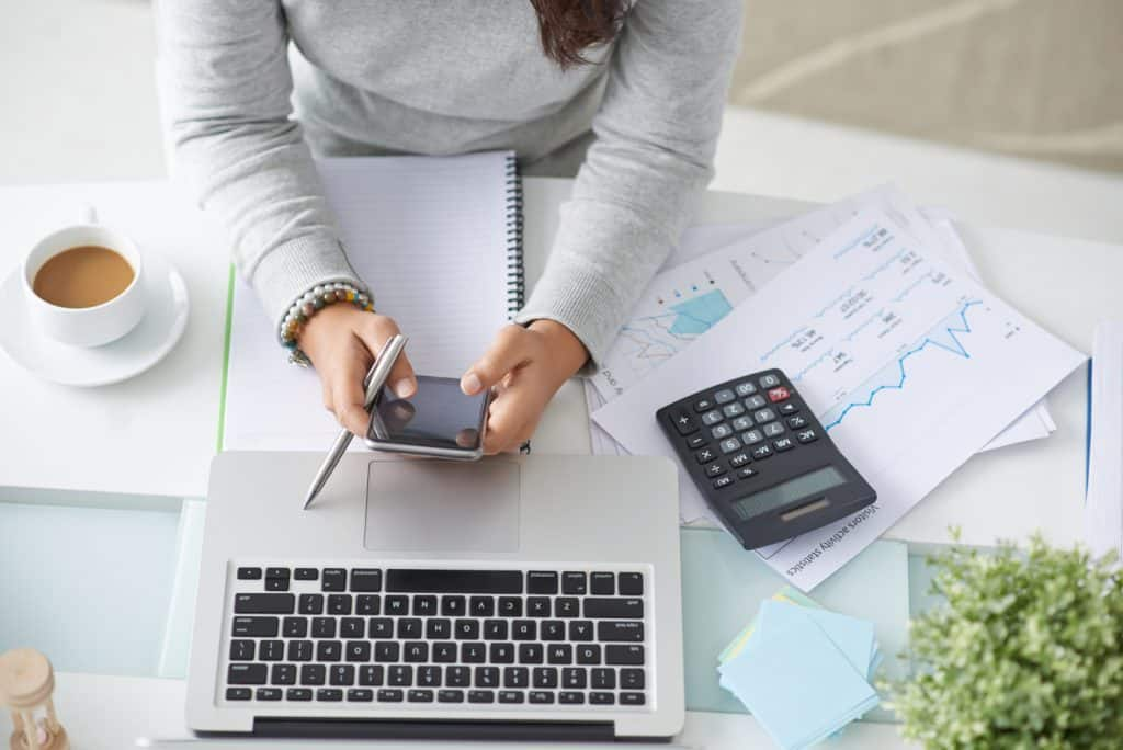 woman with calculator trying to figure out budgeting mistakes